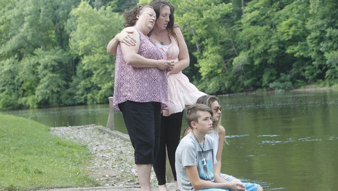 Michael Bane's family -- mother Patsy Achor, wife Autumn Bane, son and daughter, Cole Bane and Alexis, stand vigil along the spot in the Tippecanoe River with Michael was last spotted. They were holding onto hope that Michael might be OK. But about the time this photo was taken Tuesday, DNR searchers recovered a body downstream south of Indiana 18. The body has not been officially identified.