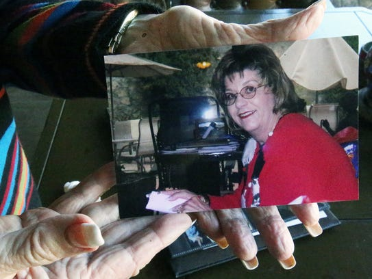 Betty Lewis holds a recent photo of her late daughter