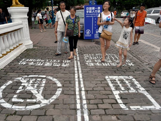 Residents walk Sept. 14 on a lane painted with instructions to separate those using their phones as they walk from others in southwest China's Chongqing Municipality.