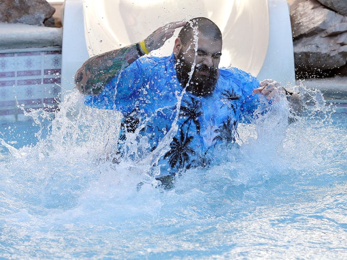 Andrew Pollia reacts as he hits the frigid water Saturday