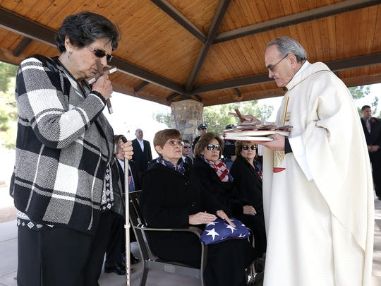 Lucy Valenzuela kisses a cross given to her by Monsignor Victor Kayrouz at her brother Armando Sambrano's funeral Friday at Fort Bliss National Cemetery. Sambrano, a World War II veteran and POW, was buried with full military honors.