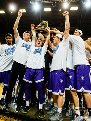 Members of the St. Thomas men's basketball team celebrate after winning the Division III national title on March 19 in Salem, Va.