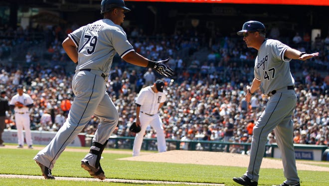 Chicago White Sox first baseman Jose Abreu rounds third base and gets a hand from coach Joe McEwing after hitting a grand slam off Detroit Tigers Anibal Sanchez, back center, in the fourth inning on Saturday April 18, 2015 in Detroit.