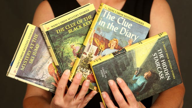 Becky Willhite discovered trading cards in four used Nancy Drew books that she purchased at the Book Bin in downtown Salem and she wonders what the story is behind them. Photo taken on Monday, Oct. 5, 2015, in Salem, Ore.