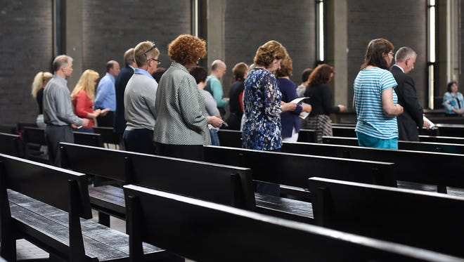People bow their heads during a prayer service Thursday, June 16, 2016, for Earl H. Potter III at the Christ Church Newman Center at St. Cloud State University.