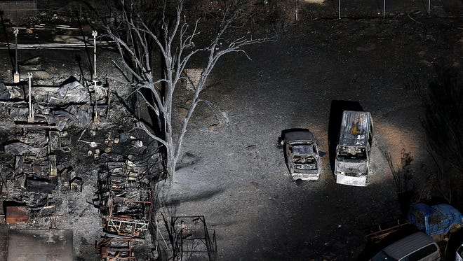 Burnt vehicles and charred debris remain following a fire in Tooele, Utah on Wednesday, July 20, 2016. Firefighters contained a blaze fueled by wind that ripped through a Utah trailer park, displacing dozens of people and destroying multiple homes.
