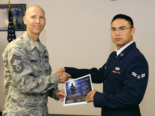 Chief Master Sgt. Gary Lawrence, 49th Operations Group chief enlisted manager, presents Airman 1st Class James Butler with a First Term Airman Course graduation certificate at Holloman Air Force Base June 29. FTAC is a program that helps first term Airmen with the transition from technical school to an operational environment. It also gives the Airmen a warm welcome to Holloman from the majority of base agencies they will be working with on a daily basis.