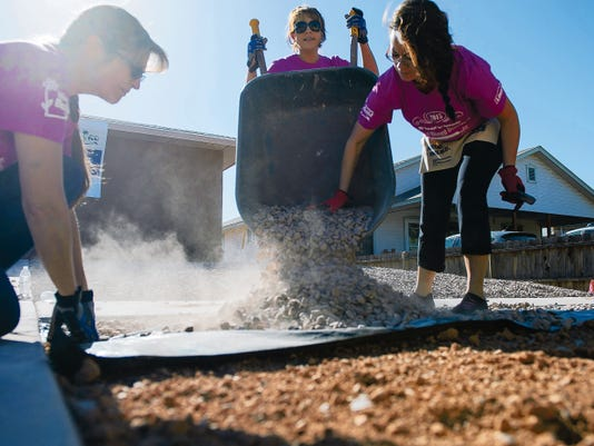 Volunteers lay gravel outside of a Habitat for Humanity construction site in downtown Alamogordo May 9. The volunteers were participating in National Women Build Week, an annual event hosted by Habitat for Humanity where multiple volunteers devote their time to come together to help the members of the community who are less fortunate by providing them with shelter above their heads.