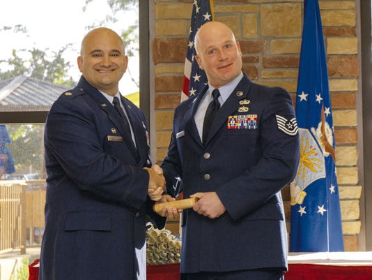 Technical Sgt. Dominic Moless, 49th Communications Squadron non-commissioned officer in charge of plans and programming and president of the Middle Two, presents a gift to Lt. Col. Matthew Sandelier, 49th Force Support Squadron commander and guest speaker for the Community College of the Air Force graduation ceremony at Holloman Air Force Base May 28. Airmen who successfully completed their CCAF degree were celebrated and awarded their diploma by Lt. Col. Ryan Craycraft, 49th Wing vice commander.