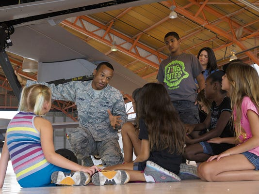 Senior Airman Elijah Rogers, a 49th Aircraft Maintenance Squadron MQ-1 Predator avionic systems journeyman, shows members from the Holloman Youth Center how light the MQ-1 is by lifting the front end off the ground at Holloman Air Force Base, N.M. on Aug. 12. Children from the youth center visited the 49th AMXS and spoke with maintainers about the capabilities of Holloman's Remotely Piloted Aircraft. The tour was also part of the Tuskegee Airmen Initiative that supports children's interest and knowledge in fields of aviation.