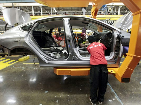 Assembly line workers build a 2015 Chrysler 200 automobile at the Sterling Heights Assembly Plant in Sterling Heights, Michigan.