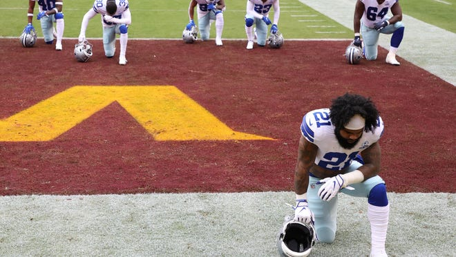 Dallas Cowboys running back Ezekiel Elliott kneels in the end zone with teammates prior to their game against the Washington Football Team at FedExField on Sunday. The Cowboys lost 25-3, sinking to 2-5 on the season.