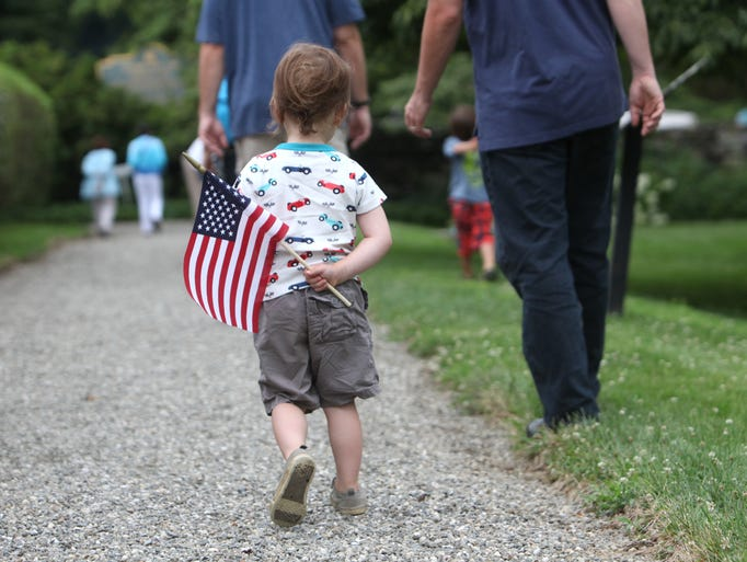 A boy walks with the American flag at the Independence Day Fair, July 4, 2014 at John Jay Homestead in Katonah. The event, hosted by the Rotary Club of Bedford-Armonk and John Jay Homestead, included colonial-era games and activities for families.