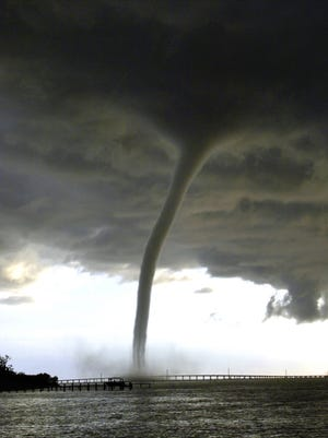 Spawned by an evening thunderstorm, a waterspout spins on the south side of the Peace River at the base of the northbound U.S. 41 bridge in Punta Gorda, Fla., Friday, July 15, 2005.