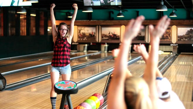 Megan Dujlovic of Niagara Falls celebrates after throwing a strike with Shane Madaus, right, of Shelby Township and Jennifer Schaub of Windsor, Ontario.