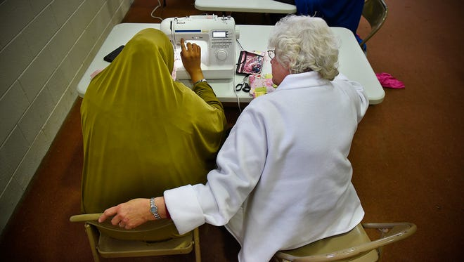 Sister Mary Obowa works with a student during a sewing class session Wednesday, Jan. 20, at First Presbyterian Church in St. Cloud.