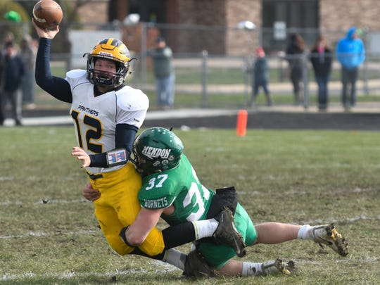 Climax-Scotts QB Dylan Butler (12) tries to dump off the pass to prevent the sack from Mendon LB Wyatt Cool (37)