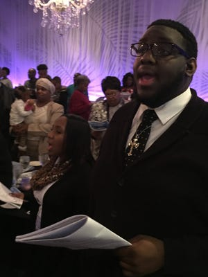 """Ciedah Roberson and DeMarco Hambrick rise to their feet to sing """"Lift Every Voice and Sing"""" with the rest of the crowd of more than 500 at Northern Kentucky NAACP's Martin Luther King Jr. luncheon in Newport."""