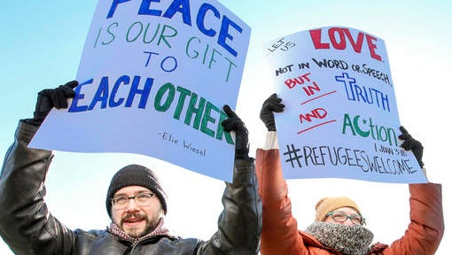 Richard Green, left and his wife Rebecca Hamlin Green, both from Owensboro, Ky., hold signs above their heads at the band shell at Smothers Park on Saturday, Feb 4, 2017, in Owensboro, Ky., while participating in an interfaith rally held by the Owensboro-Daviess County Ministerial Association. The rally, held to show interfaith support, featured religious leaders and speakers, including people who have family members in the United States on Visas.