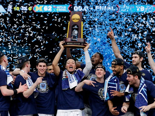 """FILE - In thisMonday, April 2, 2018 file photo, Villanova players celebrate with the trophy after beating Michigan 79-62 in the championship game of the Final Four NCAA college basketball tournament in San Antonio. Under Construction: The finishing touches on the $60-plus million renovation of Villanova's on-campus home and the national champions that will call it home. The Wildcats are certainly there among the elite after winning two national championships in three seasons, their basketball blood now as blue as the """"V"""" in their logo, reeling off 30-win seasons that's sent the 2019 forecast again sky high.  (AP Photo/David J. Phillip, File)"""