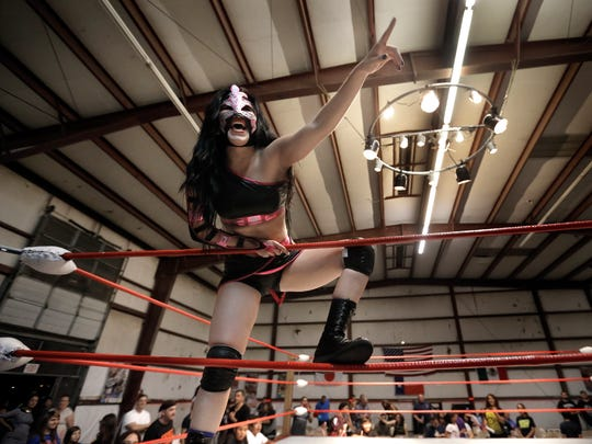 New Era Wrestling luchadora Delilah chases her opponent, Allie Kat, from the building after their match Friday.