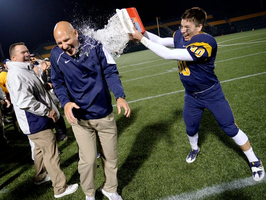 Victor head coach Geoff Mandile, left, gets doused