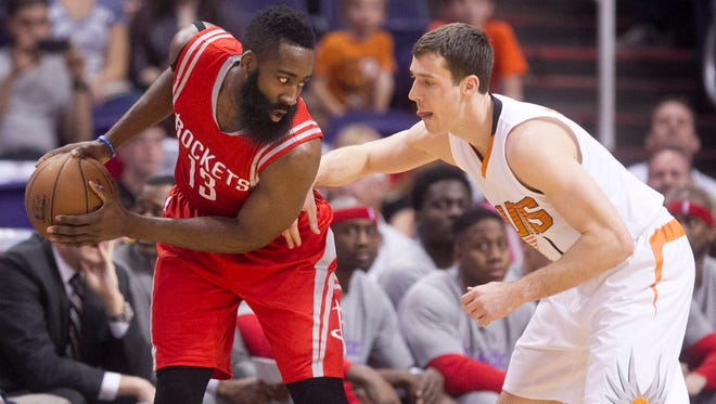 Rockets guard James Harden controls the ball as Suns guard Goran Dragic defends during the first quarter of the NBA game at the US Airways Center in Phoenix on Tuesday, February 10, 2015.