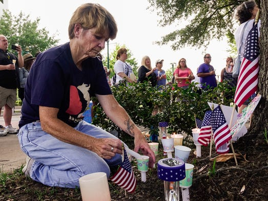 Patty Meehan lights candles during a candlelight vigil