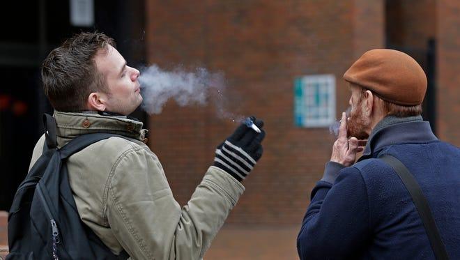 In this photo taken Thursday, Jan. 7, 2016, two men smoke outside at Seattle Central College in Seattle. A proposal in the Washington Legislature seeks to raise the smoking age to 21. (AP Photo/Elaine Thompson)