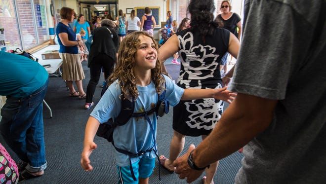 Julia Conway, a second-grader at Orchard School in South Burlington, greets her father at the end of the day on Thursday, September 8, 2016.  Teachers at the school aren't assigning homework this year.