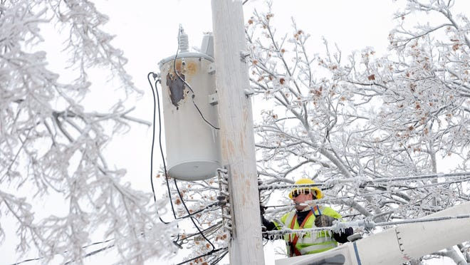 Dave Dora, a lineman from Grand Haven Board of Light and Power, works on connecting fallen wires on Macon Avenue in Lansing on Dec. 23, 2013.
