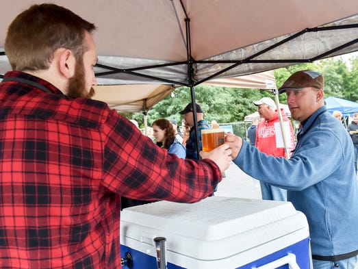 Jon Clark, left, from Roy Pitz Brewery, hands off a