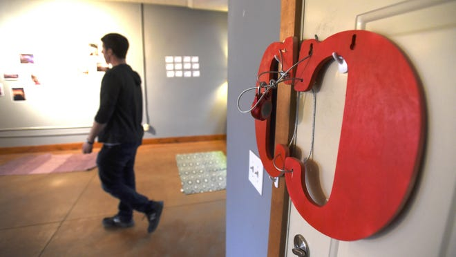 """Rabbi Dan Horowitz, founding director of The Well, walks past """"The Red Cs"""" that signify the room being locked."""