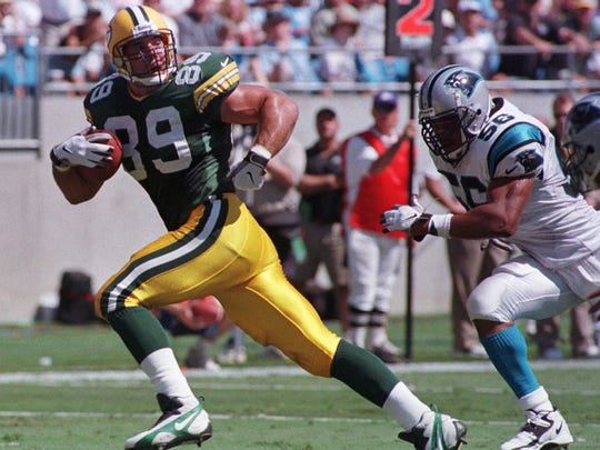 Green Bay Packers' Mark Chmura (89) glances back at Carolina Panthers' Mike Barrow (56) as he heads to the end zone for a touchdown in the first half on Sept. 27, 1998, in Charlotte, N.C.