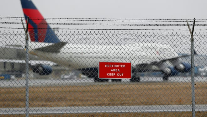 A sign is shown posted on a perimeter fence near Delta 747 aircraft taxiing at the Detroit Metropolitan Airport in Romulus, Mich., Thursday, April 9, 2015. The security fences and perimeter gates at Detroit Metropolitan Airport have been breached four times in the past two years, an Associated Press investigation shows. Nationally, at least 272 such breaches occurred at 31 major U.S. airports since the start of 2004.