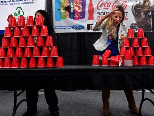 Michelle Horling (right) from Abilene Habitat for Humanity reacts as her pyramid of plastic cups partially collapses while racing against Suzanna Daniels of MetroCare in a contest Wednesday at Business EXPO.