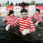 The polar plunge team Freezing Our of Our Mimes, from left, Teela Davis of Wisconsin Rapids, John G. Davis of Wisconsin Rapids, and Tori Severin of Neenah, take to the icy water at Anchor Bay Bar and Grill in Biron, Saturday, Feb. 7, 2015. An estimated 400 polar plungers raised approximately $55,000 for 1,000 area Special Olympics athletes.