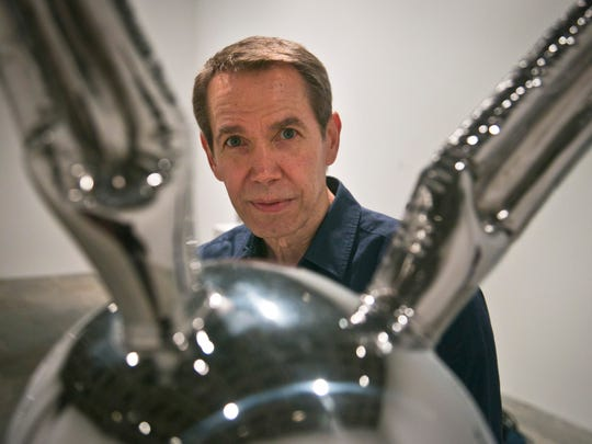 """In this file photo, Jeff Koons poses next to """"Rabbit,"""" one of his oversized toy-like sculptures among works spanning a 30-year career being installed at the Whitney Museum of American Art on Monday, June 23, 2014, in New York."""