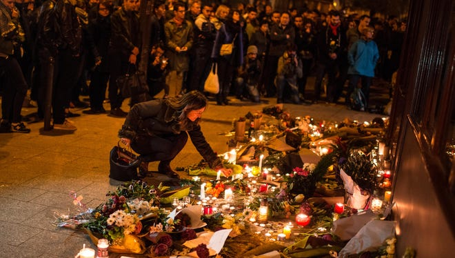 A mourner leaves candles in front of the Le Carillon restaurant on Nov. 14, 2015 in Paris following the series of terrorist attacks that struck the French capital.