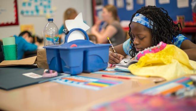 Moliena Fraser, 11, writes in her notebook during a writing workshop at Woodrow Wilson Elementary School in Binghamton.