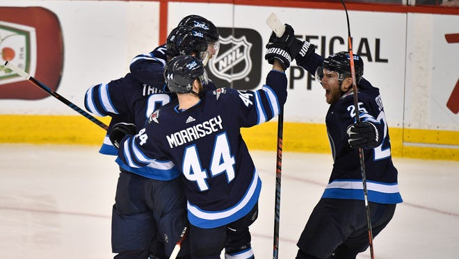 Winnipeg Jets defenseman Jacob Trouba (8) is congratulated after his goal against the Nashville Predators during the second period of Game 3 in the second-round NHL Stanley Cup playoff series at Bell MTS Place in Winnipeg, Manitoba, Canada, Tuesday, May 1, 2018.