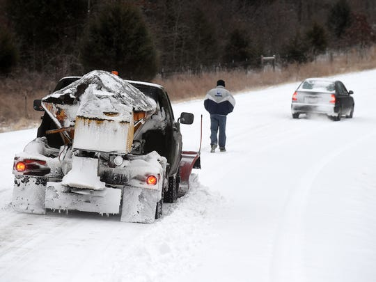 A Baxter County snow removal vehicle from the Road & Bridge Department clears snow on Hand Cove Road while a stranded motorist walks back to his car in a file photo dated February 2015.
