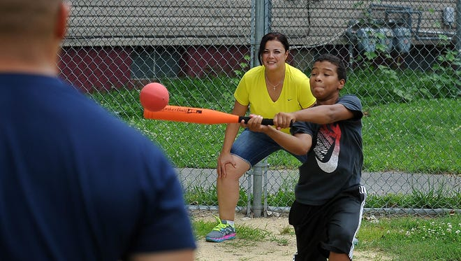 The Police Athletic League Summer Camp is underway as kids are playing softball, basketball and other activities. Chris Motter, 12, of Vineland rips a shot as Vineland police Officer Mayte Soto plays catcher on Monday.