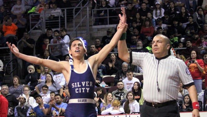 Vince Marin of Silver gets his hand raised after he won the 106-pound weight class to caputre his first state title in Rio Rancho on Saturday evening.