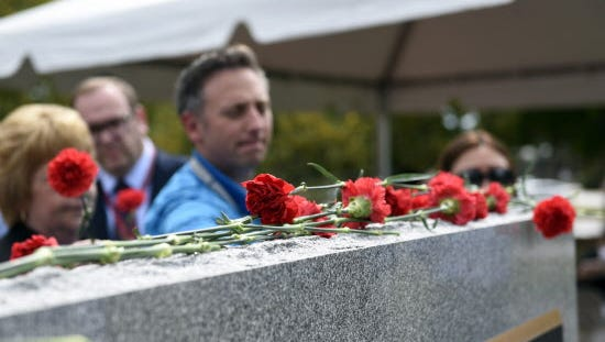 PARAMUS: Carnations are placed on the 9/11 memorial, which holds every single name of the victims of September 11, after Bergen Regional Medical Center's service on Friday.