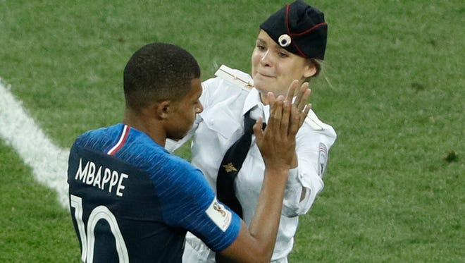 A member of Pussy Riot high-fives France's Kylian Mbappe on the pitch during the World Cup final at Luzhniki Stadium in Moscow.