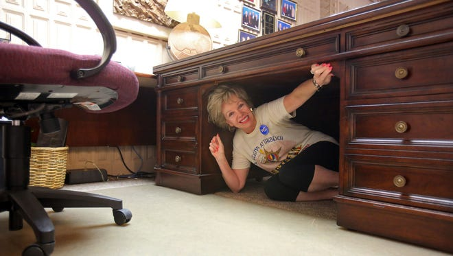 Former Rancho Mirage Mayor Iris Smotrich takes cover underneath her desk while participating in the Great California Shakeout earthquake drill at Rancho Mirage City Hall Thursday, October 16, 2014 in Rancho Mirage, Calif.