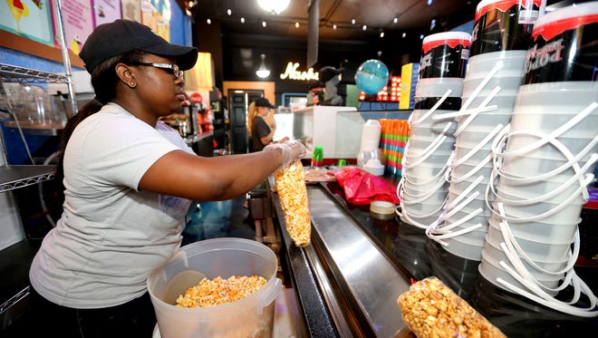 Rayna Marable bags an order of popcorn at Frozen Treats from Mars on June 20, 2016. There are more than 20 gourmet flavors of popcorn available at the Murfreesboro spot.