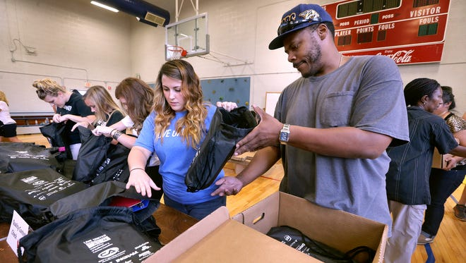 Tara Conner, left, hands backbacks to Miguel Caureso, as he packs 4 backs to each box during the Stuff the Bus event, at Hobgood, on Friday July 22, 2016.