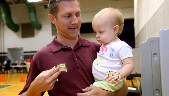 Kevin Krahenbuhl puts on his sticker after giving a sticker to his daughter Ava Krahenbuhl, 1 after voting, on Election Day Tuesday, Nov. 8, 2016, at Barfield Elementary in Murfreesboro.